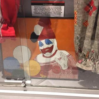 One of John Wayne Gacy's paintings of Pogo the Clown, along with part of two outfits.